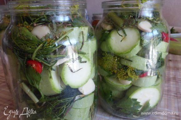 Порезанные кабачки плотно уложить в литровые банки, пересыпая порезанной зеленью, горьким перцем и чесноком.