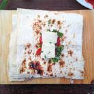 Каждый кусочек лаваша смазываем майонезом или сметаной. Посыпаем чесноком и зеленью. Раскладываем по паре кусочков помидора и сулугуни.