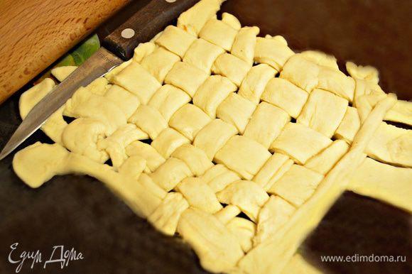 Слоёное тесто оттаять до комнатной температуры, слегка раскатать и нарезать полосками шириной около 1 см. Сформировать решётку и уложить её поверх яблок. Можно смазать сверху решётку молоком или куриным желтком.