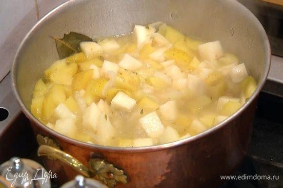 Когда лук станет мягким, добавить в кастрюлю яблоко, залить все горячим бульоном так, чтобы овощи были покрыты, снова накрыть крышкой и варить еще минут 10‒12, до готовности сельдерея и картофеля (если нужно, подлить еще бульона).