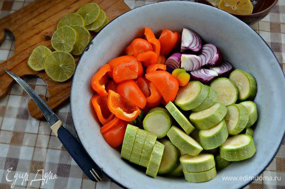 Нарежьте филе рыбы кубиками со стороной 3 см, половину лимона и лайм нарежьте тонкими кружками (крупные лимоны разрежьте на половинки или на даже четвертинки). Кабачок нарежьте кружками толщиной 0,5-0,7 см, луковицы очистите и разрежьте на четыре части. Перец очистите от семян и нарежьте кубиками примерно 4 см.