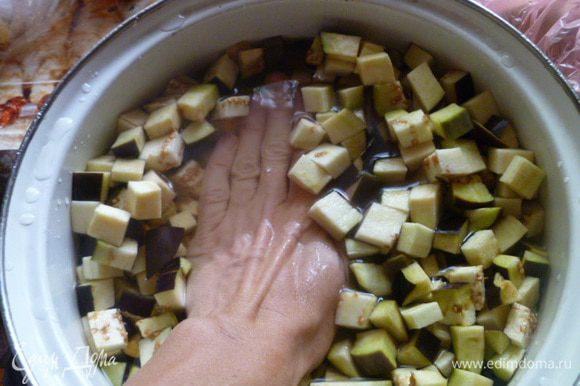Баклажаны помыть, отрезать плодоножки и нарезать кубиками. Баклажаны залить водой так, чтобы они были покрыты на 1-2 см. Добавить соль.