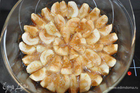 Достать из духовки форму с запеченными яблочками.