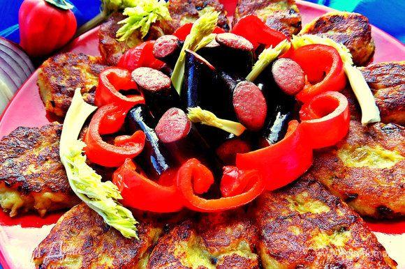 Кладём на большое блюдо золотистые оладьи. В центр высыпаем колбаски и украшаем перчиком и зеленью.