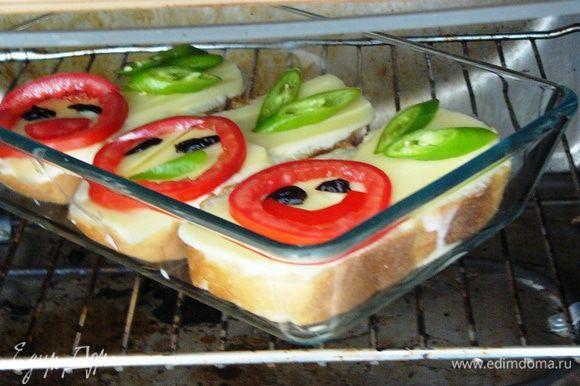 Выложить на сыр помидоры и перец в виде улыбающейся рожицы. Разместить форму с бутербродами в разогретую до 200 градусов духовку.