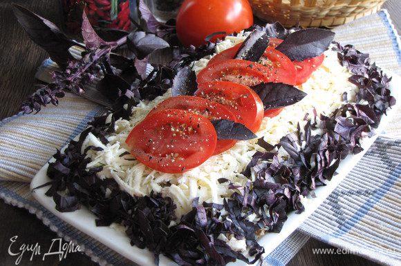 Помидор нарезать тонкими кружками и выложить на сыр. Украсить листиками базилика. Закуске дать настояться пару часов в холодильнике и можно подавать.