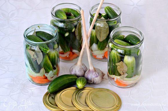 На дно стерилизованных банок уложить порезанные кольцами морковь и лук, лавровый лист, перец горошком. Уложить огурцы. Залить маринадом: В воду (4 л.) всыпать соль (4 ст. л.), сахар (9 ст. л.). Вскипятить. Убрать с огня. Дать немного остыть, примерно до 80-70 гр., влить 6 ст. л. уксусной эссенции (70%). Остудить до комнатной температуры. Залить огурцы маринадом. Пропорции ингредиентов маринада даны на 4 литра воды.