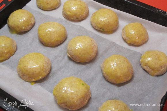 Смазать пирожки слегка взбитым желтком.