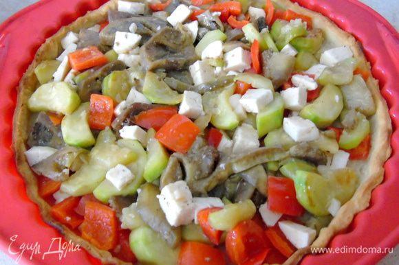 Фету поломать или нарезать кусочками. Добавить к овощам, перемешать, посолить, поперчить, выложить в полувыпеченную основу.