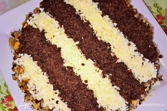 Готовые охлажденные коржи разрезаем по горизонтали, переслаиваем их кремом. Также промазываем бортики и верхушку. Орехово-шоколадной смесью, указанной в предыдущем шаге, посыпаем бока торта. Затем оформляем верх десерта стружкой из темного и белого шоколада.