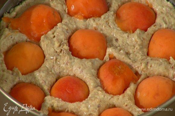 Абрикосы разделить пополам и, удалив косточки, поместить на тесто срезом вниз, слегка утапливая их.
