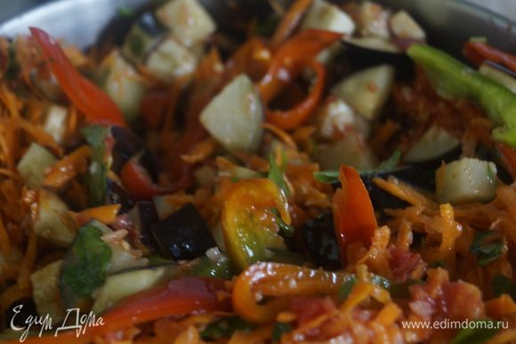 Выложить все овощи и зелень в большую кастрюлю, перемешать и залить маринадом, поставить на огонь. Готовить 40-45 минут, под закрытой крышкой, иногда помешивая.