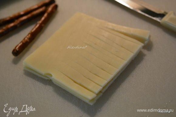 Сыр швейцарский пластинками нарезать полосками, оставив несколько сантиметров от начала.