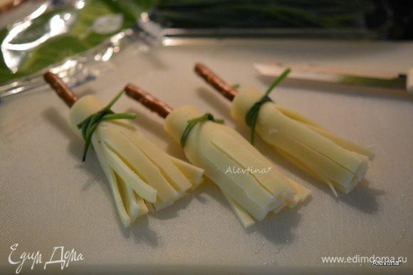 Свернуть сыр трубочкой вокруг хлебной палочки. Завязать шнитт-луком, так чтобы сыр не распался.