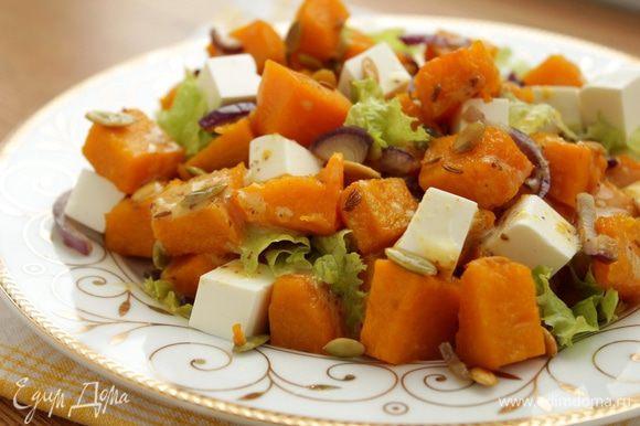 Выложите запеченные овощи и нарежьте сыр фета . Полейте заправкой.