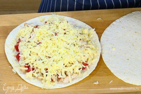 На тортилью выложить куриную начинку, посыпать натертым сыром и накрыть сверху второй лепешкой.