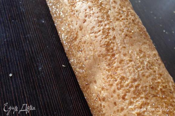 По истечении времени разогреваем духовку до 180 градусов. Достаем схватившееся тесто, убираем пленку и обваливаем колбаску в сахаре, равномерно рассыпанном на рабочей поверхности. Просто катаем тесто по столу как скалку...