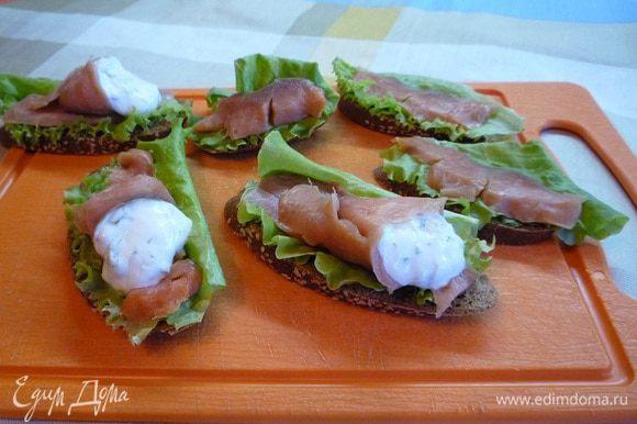 Остальные ломтики рыбы свернуть конвертиком, положить в них по ложке йогурта и выложить их сверху на бутерброды.