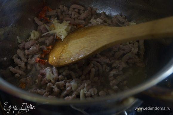 Фарш обжариваем в толстодонной кастрюле на растительном масле. Добавляем чеснок, натертый на терке и мелко рубленный перец чили.