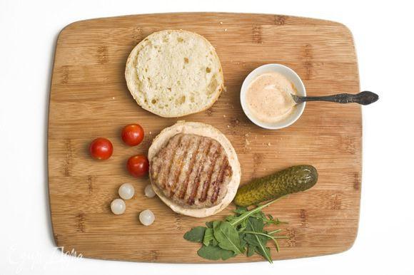 Майонез смешать с соусом чили. Булочки разрезать пополам. Смазать каждую половинку смесью майонеза и соуса чили. Затем на одну из половинок поместить котлетку и соединить половинки булочек.