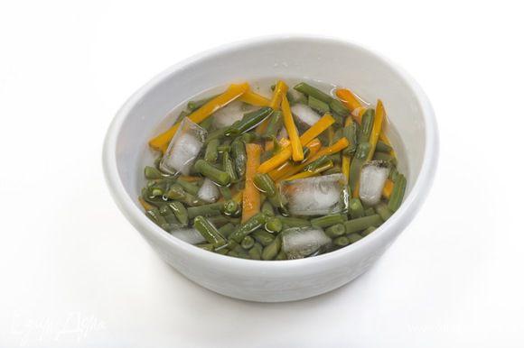 Морковь вместе со стручковой фасолью 2 минуты бланшировать в кипящей подсоленной воде, затем отправить на пару секунд в ледяную воду.