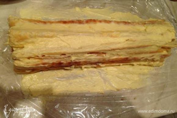 На столе расстелить пищевую пленку. Выложить на нее слой из выпеченных полосок (штучки 4). Смазать кремом. Повторять слои до окончания ингредиентов.