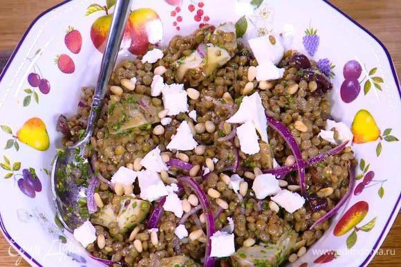 Посыпать салат обжаренными орехами.
