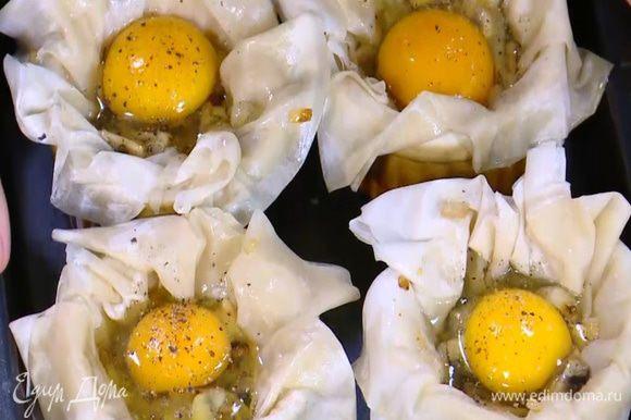Выложить в формы с тестом по 1 ст. ложке обжаренных грибов с луком и чесноком, сверху разбить по одному яйцу, посолить и поперчить.