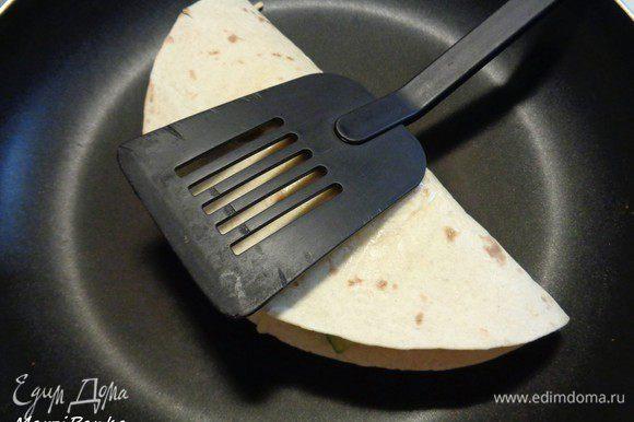 Кладем лепешку на сковородку также, чтобы слой с сыром оказался внизу, а половинка с соусом — сверху. Обжариваем кесадилью на сухой разогретой сковороде с двух сторон, прижимая лопаткой. Буквально по паре минут с каждой стороны. Как сыр подтаял — переворачиваем. Огонь делаем средний, чтобы ничего не пригорело.