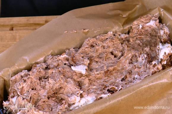 Прямоугольную форму для кекса выстелить бумагой для выпечки, выложить тесто и разровнять его.