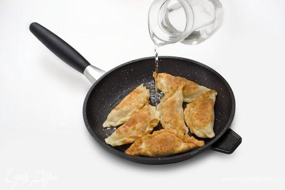 На разогретую сковороду налить кунжутное масло, выложить яки гедза вверх защипами. Держать до появления золотистой корочки, затем уменьшить огонь. Долить в сковороду воды, примерно до середины высоты яки гедза. Накрыть крышкой и готовить около 15 минут.