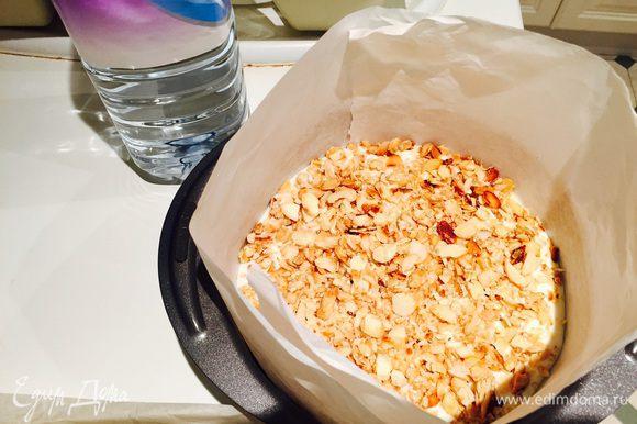 Выливаем на него немного крема, укладываем бисквитный корж. Потом много крема (чуть меньше чем половина). Щедро засыпаем все нашими орешками.
