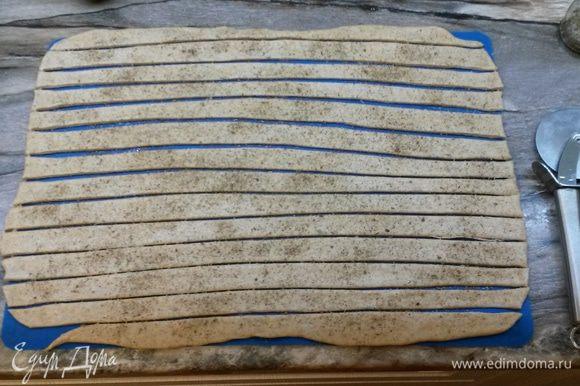 Смазываем тесто водой, посыпаем сухими травами или маком. Ножом для пиццы разрезаем тесто на полоски шириной 1.5 см.