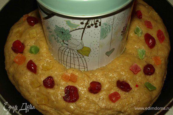 Когда тесто подойдет, выбиваем его и формируем толстое бревно и соединяем концы. Делаем кольцо и перекладываем на смазанный маслом противень (форму). Раскладываем сверху цукаты и засахаренные (вяленые) фрукты/ягоды. В центр кольца поставить смазанную маслом емкость, чтобы сохранить форму кольца. Накрываем и оставляем, примерно на 1 час подходить.
