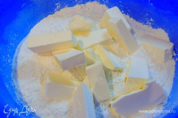 В просеянную муку добавляем соль, сахар и кусочками нарезанное сливочное масло.