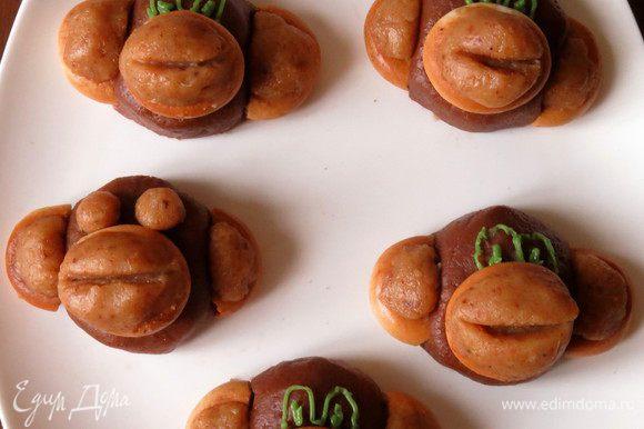 Рисуем глаза сахарной глазурью или делаем глаза в виде шариков из светлой массы. Подаем сладости — из трубочек и мандаринок делаем пальму, посыпаем на тарелку сахарную глазурь для украшения — песок.