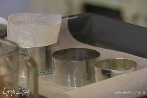 Выстелить противень бумагой для выпечки, смазать ее сливочным маслом, поставить на нее кольца для выпечки и выстелить их изнутри бумагой для выпечки, смазанной сливочным маслом.