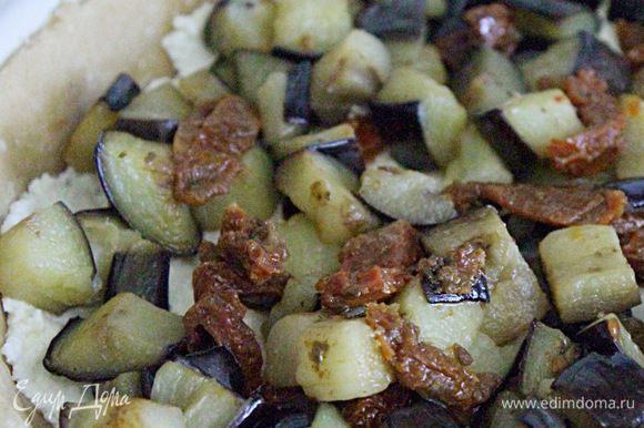 Моцареллу натереть на тёрке, половину смешать со сливочным сыром и выложить на основу. Сверху разместить баклажаны и вяленые помидоры.