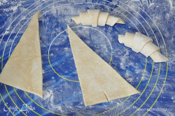 Это тесто не нуждается в раскатывании. Тесто разделить на 2 равных прямоугольника, каждый разрезать на 2 треугольника. Треугольник надсечь у основания, скрутить тесто от широкого края к узкому, спрятать узкий край под круассан. Придать форму полумесяца, выложить на противень, застеленный бумагой для выпечки. Накрыть салфеткой и дать подойти тесту в течение 1,5 часов.