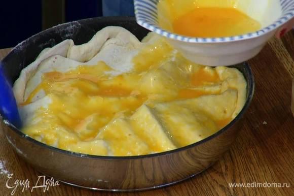 Желтки посолить, перемешать с молоком и кисточкой смазать тесто.