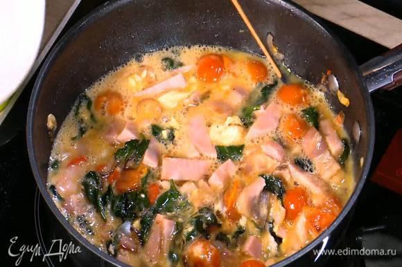 Яйца и белки перемешать венчиком, посолить, поперчить и влить в сковороду с овощами и ветчиной. Обжарить все вместе, постоянно помешивая, затем снять сковороду с огня.