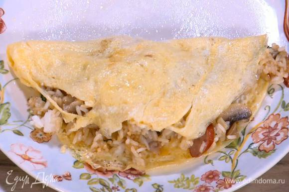 Завернуть в яичные блинчики рис с колбасками и беконом.