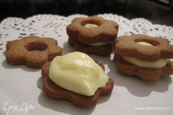 На одну половину остывшего печенья нанести крем и накрыть второй половинкой.