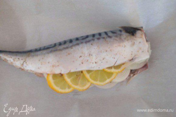 Из оставшейся половины лимона выжимаем сок и сбрызгиваем им рыбу, солим, перчим и помещаем в брюшко лук и лимон. Теперь кладем подготовленную рыбку на противень, выстланный пергаментной бумагой, смазываем сметаной и заворачиваем, как конфету и ставим в разогретую до 180°C духовку на 30-35 минут. За 5 минут до готовности бумагу развернуть и переключить духовку в режим гриля, чтобы рыбка подрумянилась немного.
