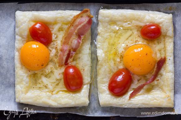 Достаньте пирог из духовки, и немного надавите на внутреннюю часть. Аккуратно выложить в центр тертый сыр, бекон и помидоры черри. Разбейте яйца в середину каждого пирога, верните в духовку еще на 10-15 минут, или до готовности яиц.