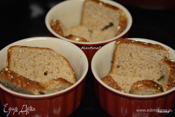 Разогреть духовку до 180°C. Смазать порционные формочки для запекания маслом. Выложить в формы по куску хлеба. Можно белый или ржаной. У меня цельнозерновой.