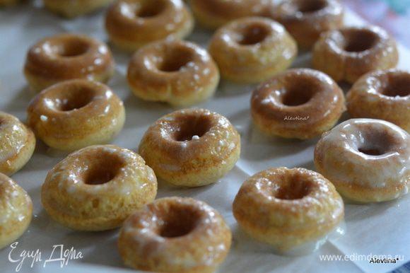 Окунать каждый пончик в глазури и выкладывать на противень или место с бумагой для выпечки.