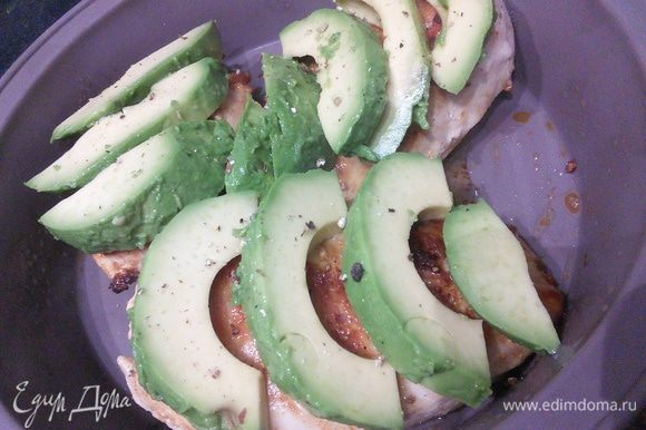 Затем выложить филе в форму для запекания, покрыть мясо пластинками авокадо.
