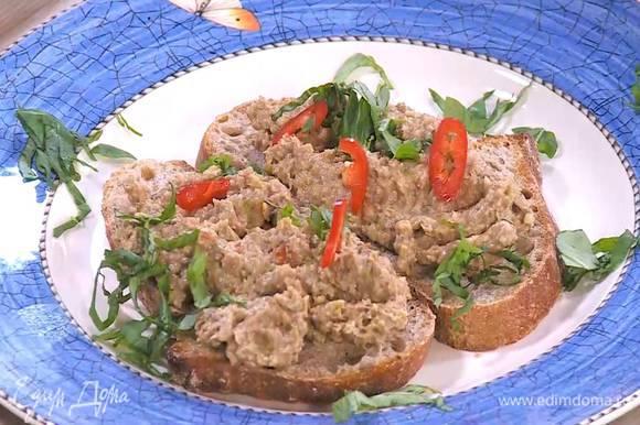 Теплый хлеб смазать паштетом, посыпать перцем чили и базиликом.