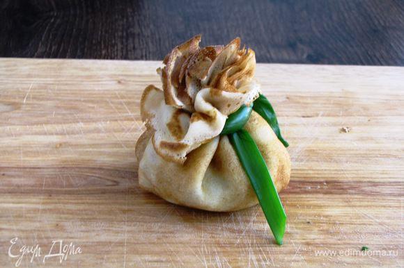 Соберите края блинчика вокруг начинки, образуя складки, и завяжите перышком зеленого лука. Торба готова.